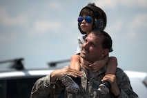 An Airman watches aircraft flying by with his son during Tampa Bay AirFest 2018 at MacDill Air Force Base, Fla., May 11, 2018. Over a three-day span, approximately 150,000 attendees experienced aerial demonstrations and interactive static displays. (U.S. Air Force photo by Airman 1st Class Ashley Perdue)