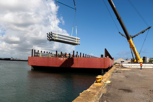 FEMA contractors unload utility poles from the barge Atlanta Bridge at Port of San Juan, Puerto Rico, May 2.