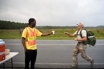 Airman 1st Class Robert Moses, 822d fireteam member, offers water to a participant during a Law Enforcement memorial 5k run and rucksack march, May 17, 2018, at Moody Air Force Base, Ga. President John F. Kennedy signed a proclamation in 1962 designating may 15 as Peace Officers Memorial Day.  Security Forces Members used Police Week to promote camaraderie and recognize all law enforcement members who have lost their lives in the line of duty. (U.S. Air Force photo by Senior Airman Daniel Snider)