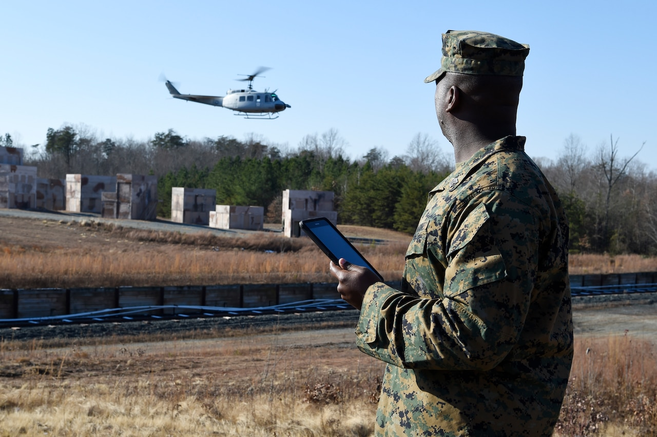 "Marine Corps Sgt. Dionte Jones watches as an UH-1 ""Huey"" helicopter equipped with the Office of Naval Research-sponsored Autonomous Aerial Cargo Utility System kit departs the landing zone following a resupply mission he requested using a handheld tablet at Marine Corps Base Quantico, Va."