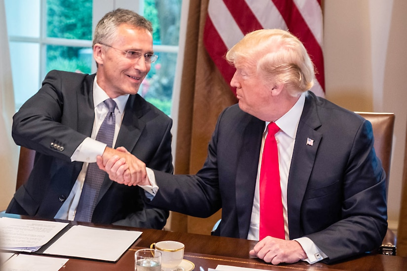The president and NATO secretary general sit at a table and shake hands.