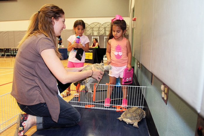 Mary Lane Poe, biologist, External Affairs, Marine Corps Air Ground Combat Center, Twentynine Palms, Calif., shows young attendees of the Combat Center School Liaison's annual Kindergarten Parent Transition Workshop the base's ambassador tortoises, Thelma and Louise, May 9, 2018. The event drew 38 parents and 32 children. (U.S. Marine Corps photo by Kelly O'Sullivan)