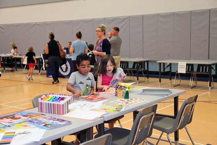 Young attendees of the Combat Center School Liaison Kindergarten Parent Transition Workshop color while their parents gather information May 9, 2018. The event at the MCCS Community Center aboard Marine Corps Air Ground Combat Center, Twentynine Palms, Calif., drew 38 parents and 32 children. (U.S. Marine Corps photo by Kelly O'Sullivan)