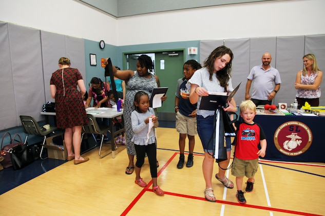 Families enter the MCCS Community Center aboard Marine Corps Air Ground Combat Center, Twentynine Palms, Calif., May 9, 2018, for the annual Combat Center School Liaison Kindergarten Parent Transition Workshop. The event drew 38 parents and 32 children. (U.S. Marine Corps photo by Kelly O'Sullivan)