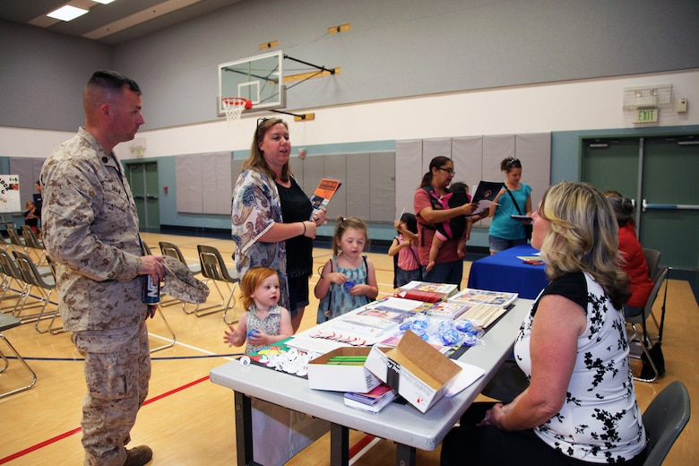 Staff Sgt. Alan Shaw, 3rd Battalion, 11th Marine Regiment, his wife, Kylie, and daughters, Nora, 2, and Ainsley, 4, chat with representatives of Twentynine Palms Head Start during the Combat Center School Liaison's annual Kindergarten Parent Transition Workshop, May 9, 2018. The event at the MCCS Community Center aboard Marine Corps Air Ground Combat Center, Twentynine Palms, Calif., drew 38 parents and 32 children. (U.S. Marine Corps photo by Kelly O'Sullivan)