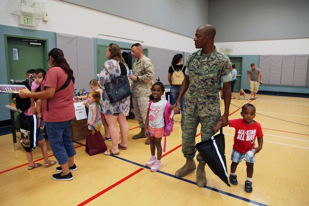 Staff Sgt. Abayomi Adeniyi, instructor, Charlie Company, Marine Corps Communication-Electronics School, walks through the Combat Center School Liaison Kindergarten Parent Transition Workshop with his 4-year-old daughter, Grace, and 2-year-old son, Samuel, May 9, 2018. The event at the MCCS Community Center aboard Marine Corps Air Ground Combat Center, Twentynine Palms, Calif., drew 38 parents and 32 children. (U.S. Marine Corps photo by Kelly O'Sullivan)