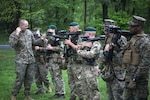 Marines and British commandos stand together holding guns during a military exercise.