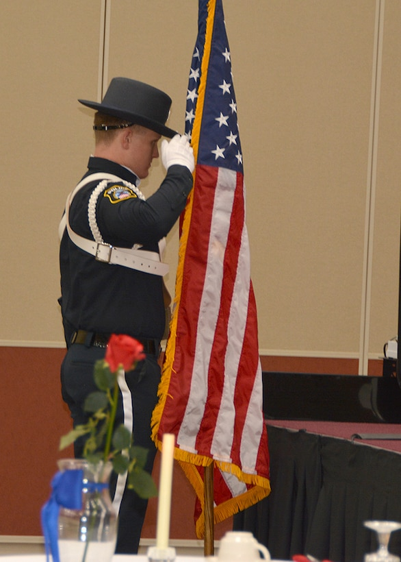 Officer salutes flag during ceremony