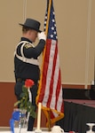 Defense Logistics Agency Installation Operations at Richmond's Police Officer Randy Guratosky salutes the U.S. Flag after posting the colors during a National Police Week ceremony held May 17,  2018 in the Frank B. Lotts Conference Center on Defense Supply Center Richmond, Virginia.  In the foreground is the Table of Honor representing those fallen law enforcement officers no longer with us.