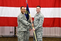 Col. André A. McMillian, 94th Maintenance Group commander, passes the 94th MXG guidon to Maj. Wade Smith during an assumption-of-command ceremony at Dobbins Air Reserve Base, Ga. on May 5, 2018. Smith formally assumed command of the 94th Aircraft Maintenance Squadron during the event. (U.S. Air Force photo/Senior Airman Josh Kincaid)