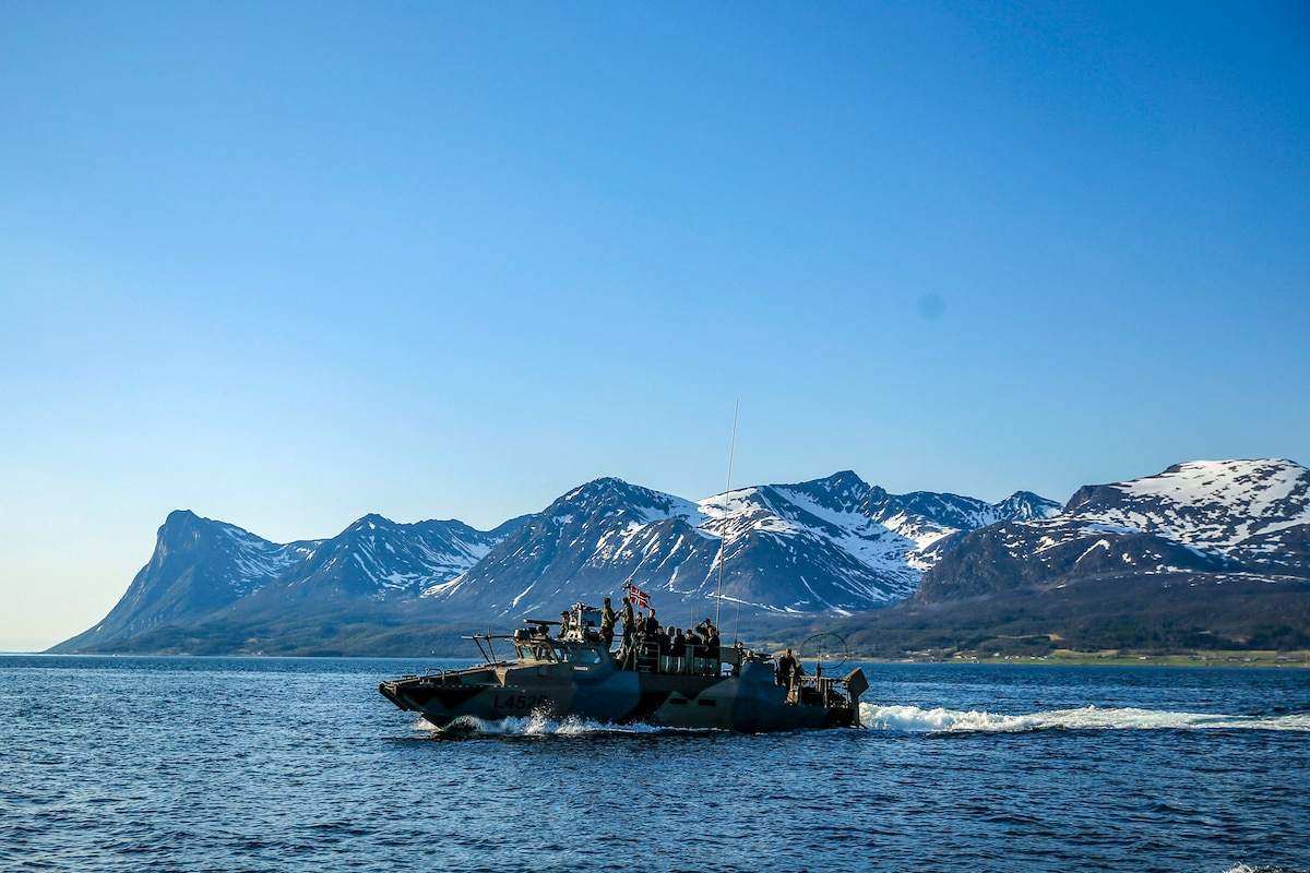 A fast assault craft travels in water with snow-capped mountains in the background.