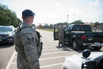 Senior Airman Zachary Vega, 81st Security Forces Squadron instillation patrolman, takes control of a role player during an exercise situation at a gate during a ride-along at Keesler Air Force Base, Miss., May 17, 2018. The ride-along program is part of the 81st SFS community involvement initiative where anyone, age 15 and up and with base access, can see what it's like to be a defender. If you are interested in the ride-along program, please contact Tech. Sgt. Matthew Oleson at 228-376-6601. (U.S. Air Force photo by Senior Airman Travis Beihl)
