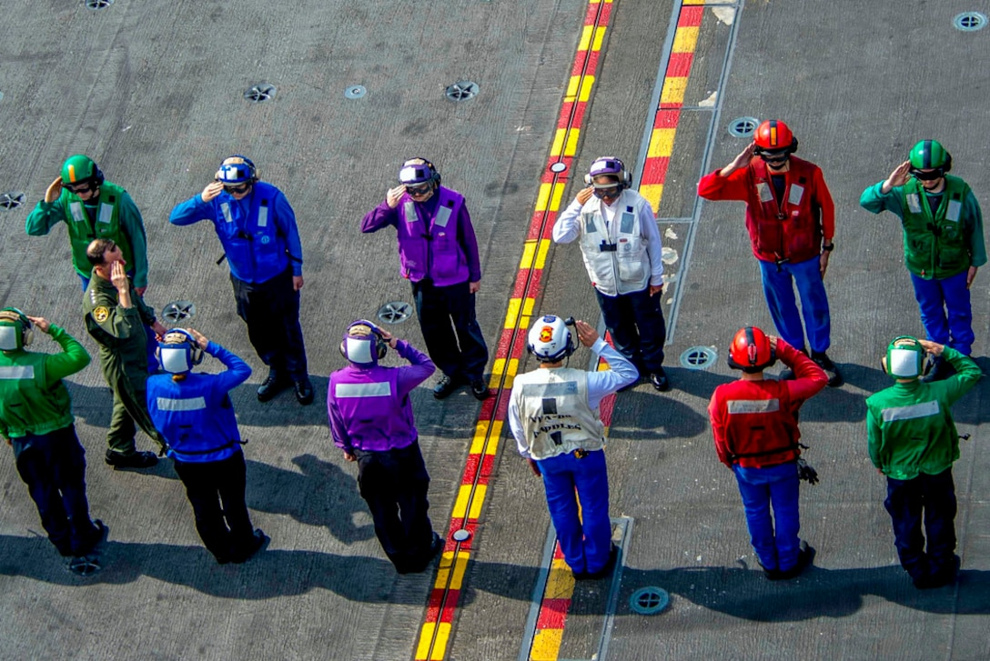 Two rows of sailors in uniforms of different primary colors salute.