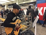 U.S. Tech. Sgt. Oliver Dagum sings and plays guitar by the S train at Grand Central Station, New York, New York. Dagum is a Ramp Services Supervisor at the 88th Aerial Port Squadron, 514th Air Mobility Wing, Joint Base McGuire-Dix-Lakehurst, New Jersey. (U.S. Air Force photo by 1st Lt. Emily Rautenberg)