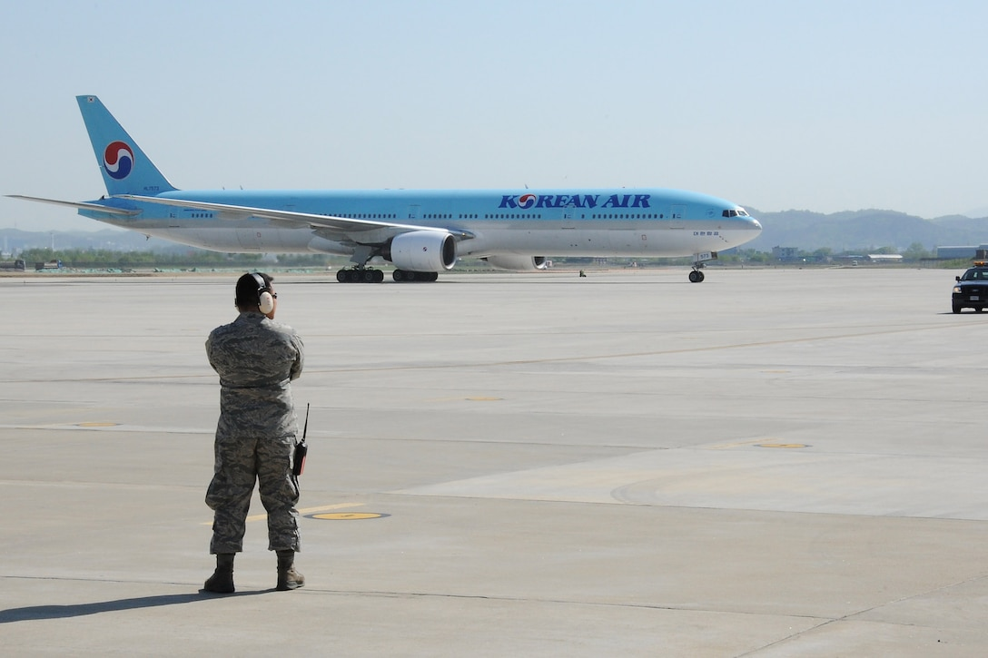 U.S. Air Force 1st Lt. Roed Mejia, 731st Air Mobility Squadron passenger services flight commander, prepares to direct an incoming Korean Air Boeing 777 aircraft during a Mutual Airlift Support Agreement (MASA) exercise at Osan Air Base, Republic of Korea, May 4, 2018. The MASA demonstrates the alliance between the United States and ROK, which enabled the 731st AMS to process passengers and load personnel baggage onto a Korean commercial aircraft. (U.S. Air Force photo by Tech. Sgt. Ashley Tyler)