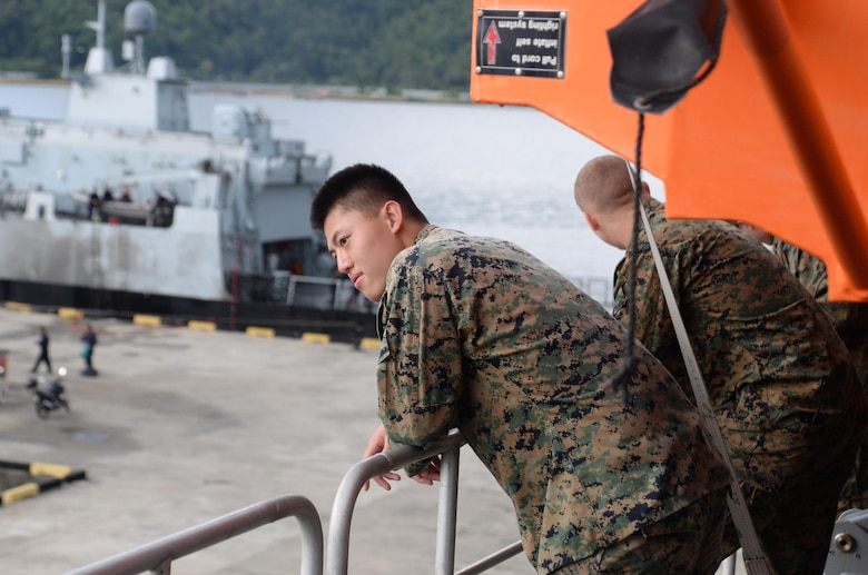 Cpl. Chun Chan, assigned to Fleet Anti-terrorism Security Team Pacific (FASTPAC) piers over the side of USNS Millinocket (T-EPF 3) as the ship pulls pierside in Seppangar Naval Base during a U.S. 7th Fleet theater security cooperation patrol. Millinocket will visit several countries in the Indo-Pacific in the coming weeks.