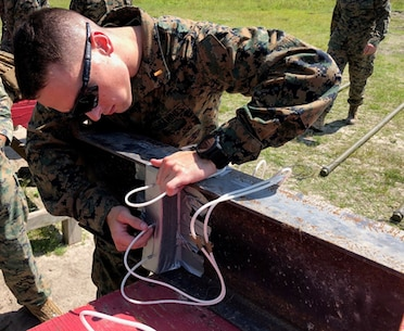 On May 10 2018, Second Lieutenant Trevor Kenahan, a student with Combat Engineer Officer course 2-18 (CEO 2-18), primes a steel I-beam charge as part of a military demolitions practical application.