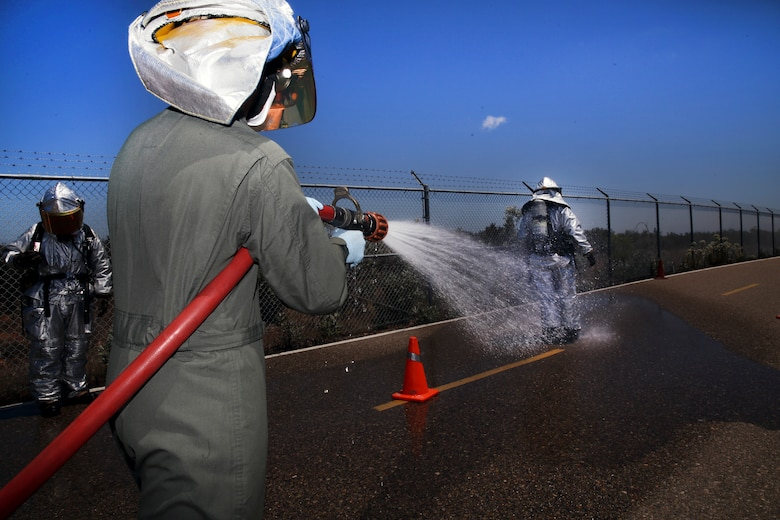 Pfc. Connor Mize, a hazardous material entry team technician with Aircraft Rescue and Fire Fighting, douses Lance Cpl. Luis Da Luz, a HAZMAT entry team technician with ARFF, with a fire hose during the decontamination process of a chemical, biological, radiological, nuclear and high-yield explosive exercise conducted at Marine Corps Air Station Miramar, California, May 17, 2018. The exercise simulated a bioterrorism attack and required several MCAS Miramar units to coordinate an effective response.