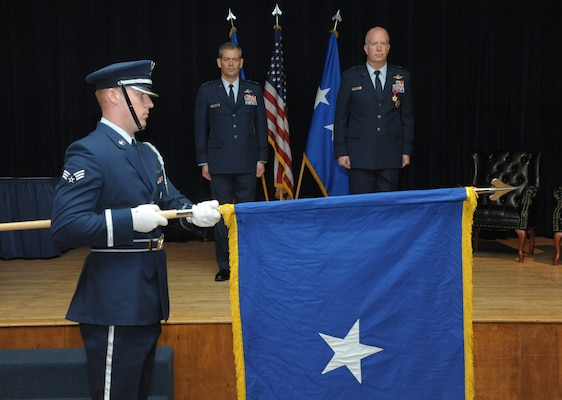 Lt. Gen. Kenneth Wilsbach, commander of Alaskan North American Aerospace Defense Command Region, Alaskan Command, U.S. Northern Command, and Eleventh Air Force, and Col. Joel Carey stand at attention during the personal colors unfurling during Carey's promotion to brigadier general, May 18, 2018, Joint Base San Antonio-Randolph, Texas. The 12FTW is responsible for four single-source aviation pipelines – Pilot Instructor Training, Combat Systems Officer Training, Remotely Piloted Aircraft Pilot Indoctrination, and Basic Sensor Operator Qualification. (U.S. Air Force by Joel Martinez)