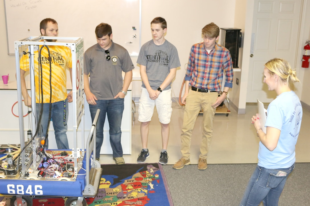 Olga Oakley, the Hands-On Science Center Air Force STEM director, at right standing, asks the Central Magnet Robotics team about their trip to the FIRST® Robotics World Championship in Houston, Texas. The Central Magnet Robotics team visited the HOSC in Tullahoma May 1 to give a demonstration. Pictured, starting left standing, are Aidan Gibson, Jimmy Jones, David Schafer, Drew Dove, Marc Guthrie, Olga Oakley, Maddy Perrien and Ethan Davenport. (U.S. Air Force photo/Deidre Ortiz)