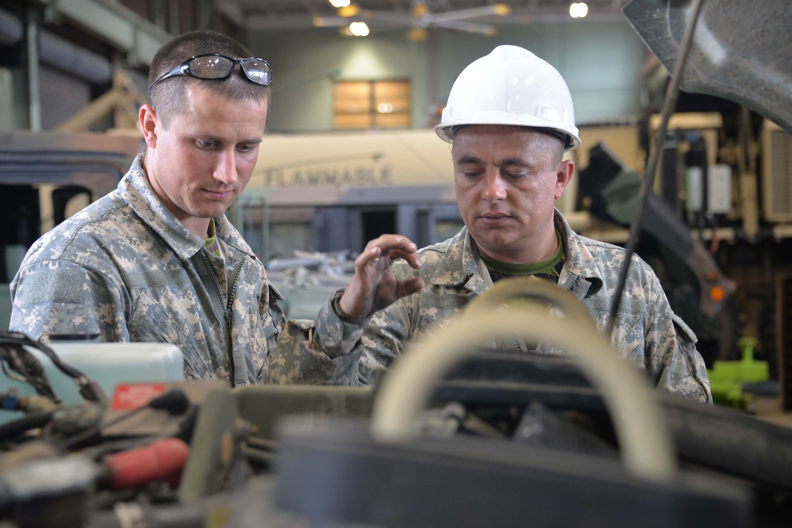 Warrant Officer Ghenadie Varzari and SGT Andrei Dogari, Mechanics with the Moldovan Defense Forces, work together to troubleshoot the issue in a Humvee engine at the North Carolina National Guard Combine Support Maintenance Shop in Raleigh, North Carolina, May 17, 2018. The North Carolina National Guard and the Moldovan Defense Forces have been hosting bi-lateral engagements through the State Partnership Program that has allowed Soldier growth and development for both countries.