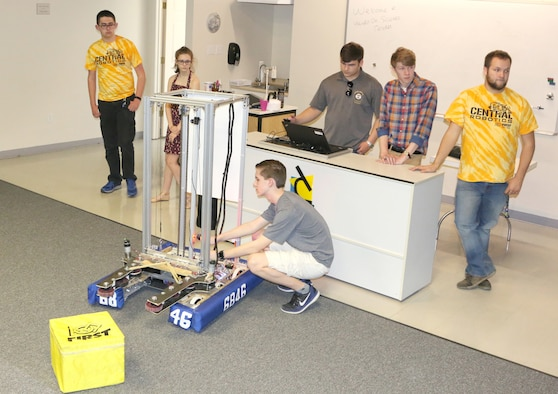 Central Magnet Robotics team member David Schafer adjusts the robot during the team's demonstration at the Hands-On Science Center in Tullahoma May 1. Pictured in back, from left to right, are Ethan Davenport, Maddy Perrien, Jimmy Jones, Drew Dove and Aidan Gibson. (U.S. Air Force photo/Deidre Ortiz)