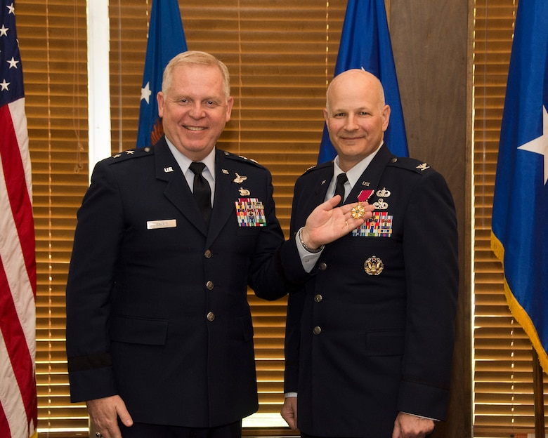 During a retirement ceremony held for Col. Raymond Briggs, right, May 11 at Arnold Lakeside Center, Maj. Gen. David Harris, left, Air Force Test Center commander, pins the Legion of Merit medal onto Briggs' lapel. The Legion of Merit is an award given for exceptionally meritorious conduct in the performance of outstanding services and achievements. Briggs is retiring this month from his position as chief of the Test System Sustainment Division at Arnold Engineering Development Complex. (U.S. Air Force photo/Rick Goodfriend)