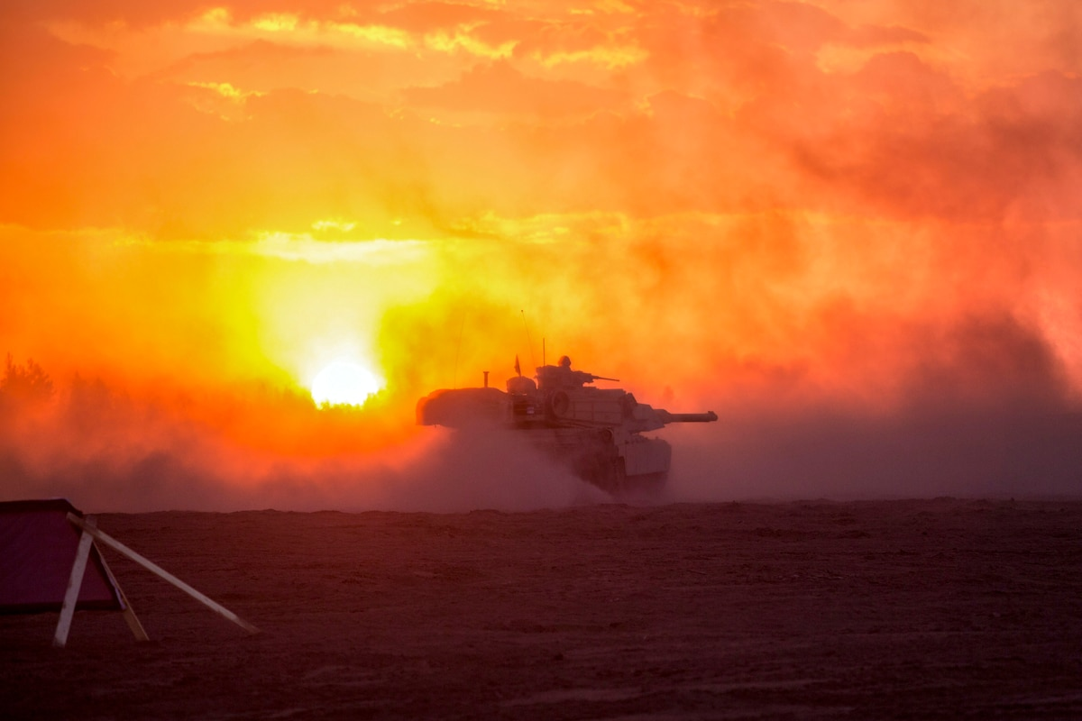 A tank kicks up sand while driving on a field, illuminated by orange sky.