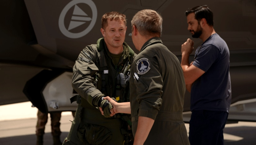 Lt. Col. Martin Tesli, 62nd Fighter Squadron, F-35 instructor pilot, shakes hands with Maj. Brian Bann, Defense Contract Management Agency F-35 pilot, upon arriving June 29, 2017, at Luke Air Force Base, Ariz. Receiving its 57th F-35, Luke continues to build the future of airpower.