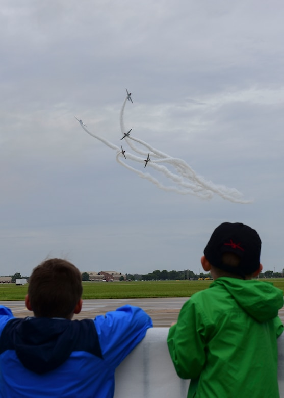 Children watch the Geico Skytypers perform during the AirPower Over Hampton Roads JBLE Air and Space Expo at Joint Base Langley-Eustis, Virginia, May 19, 2018. The Geico Skytypers team consists of six vintage U.S. Navy SNJ trainers that display tactical maneuvers used during World War II and the Korean War. (U.S. Air Force photo by Airman 1st Class Monica Roybal)