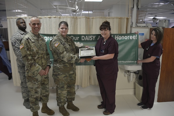 Col. Margaret Nava, Brooke Army Medical Center chief nursing officer, presents Arlene Johnson, Neonatal Intensive Care Unit registered nurse, the Daisy Award during a ceremony at Brooke Army Medical Center May 16.