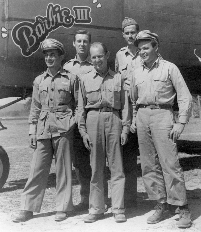 Phil Cochran (right) and Johnny Alison (center) with air commandos by the Barbie III aircraft.