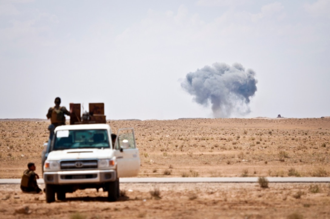 Syrian Democratic Forces watch as a coalition airstrike hits its target on a known Islamic State of Iraq and Syria location near the Iraq-Syria border.