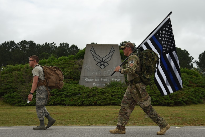 U.S. Air Force Airman 1st Class Christopher Rippin, 20th Security Forces Squadron (SFS) installation entry controller, left, and Tech. Sgt. Justin Bell, 20th SFS standards and evaluation technician, participate in a National Police Week March for the Fallen at Shaw Air Force Base, S.C., May 17, 2018.