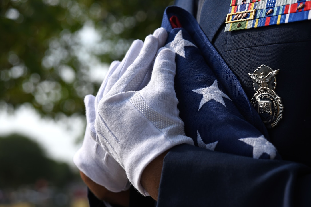 U.S. Air Force Tech. Sgt. Derek Smiling, 20th Security Force Squadron flight sergeant, holds a U.S. flag prior to a National Police Week opening ceremony at Shaw Air Force Base, S.C., May 14, 2018.