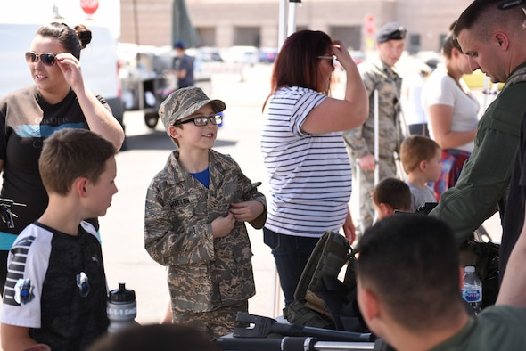 Conor Hutton, center, the son of Heather, far left, and U.S. Air Force Senior Airman Michael Hutton, 460th Security Forces Squadron patrolman, learns about the safety equipment worn by defenders during a Police Week demonstration at Buckley Air Force Base, Colorado, May 17, 2018.