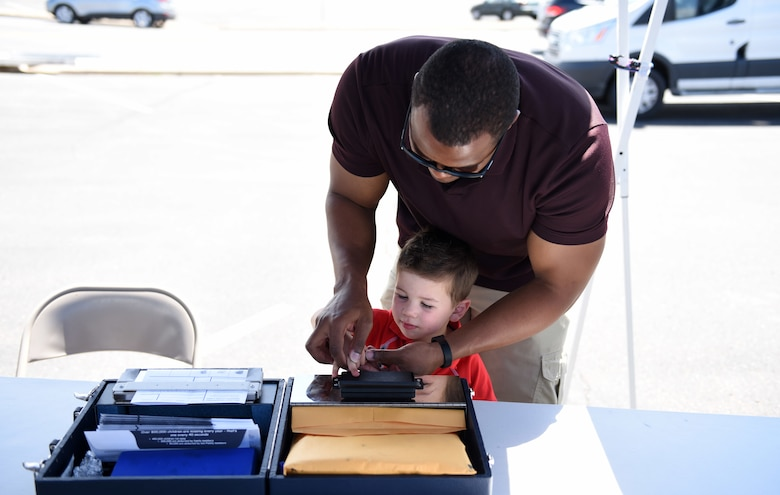 U.S. Air Force Tech. Sgt. Antonio Burton, 460th Security Forces Squadron investigator, provides fingerprints for Connor Collier, the son of Heather and Tech. Sgt. Bryan Collier, 460th SFS visitor center NCO in charge, as part of a Police Week demonstration at Buckley Air Force Base, Colorado, May 17, 2018.