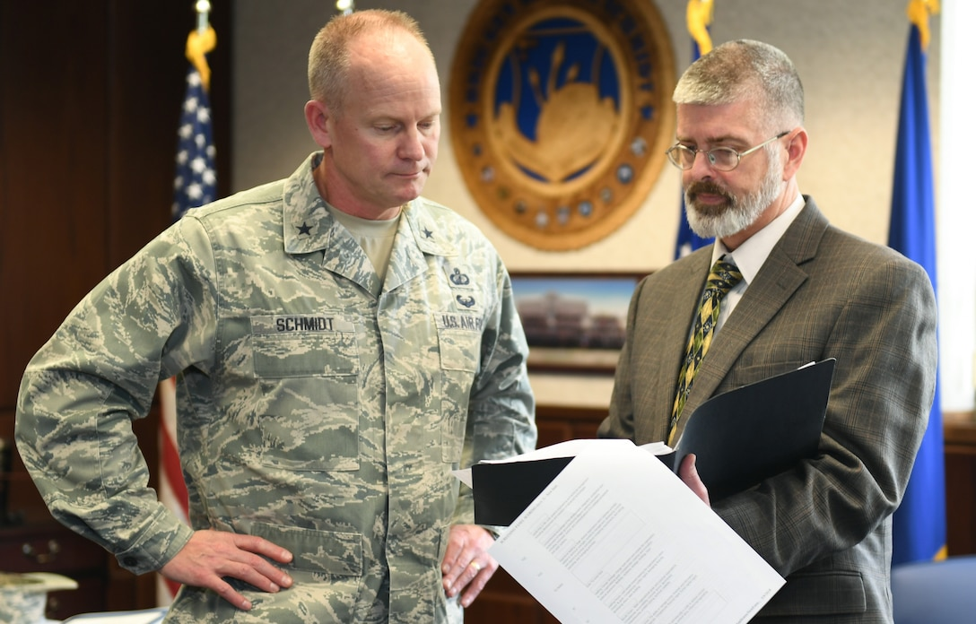 Program Executive Officer for Command, Control, Communications, Intelligence and Networks Brig. Gen. Michael Schmidt looks over acquisition strategies with his deputy, Scott Owens, at Hanscom Air Force Base, Mass., Friday, May 18. Schmidt and Owens recently took over leadership of the C3I&N directorate in April and say they are working towards enabling a workforce which acquires systems at the speed technology evolves. (U.S. Air Force Photo by Todd Maki)