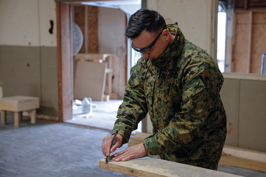 U.S. Marine Cpl. Junior G. Moncayo, heavy equipment mechanic with Bridge Company B, 6th Engineer Support Battalion, 4th Marine Logistics Group, draws a cut line on a wooden plank at a construction site during exercise Red Dagger at Fort Indiantown Gap, Pa., May 19, 2018.