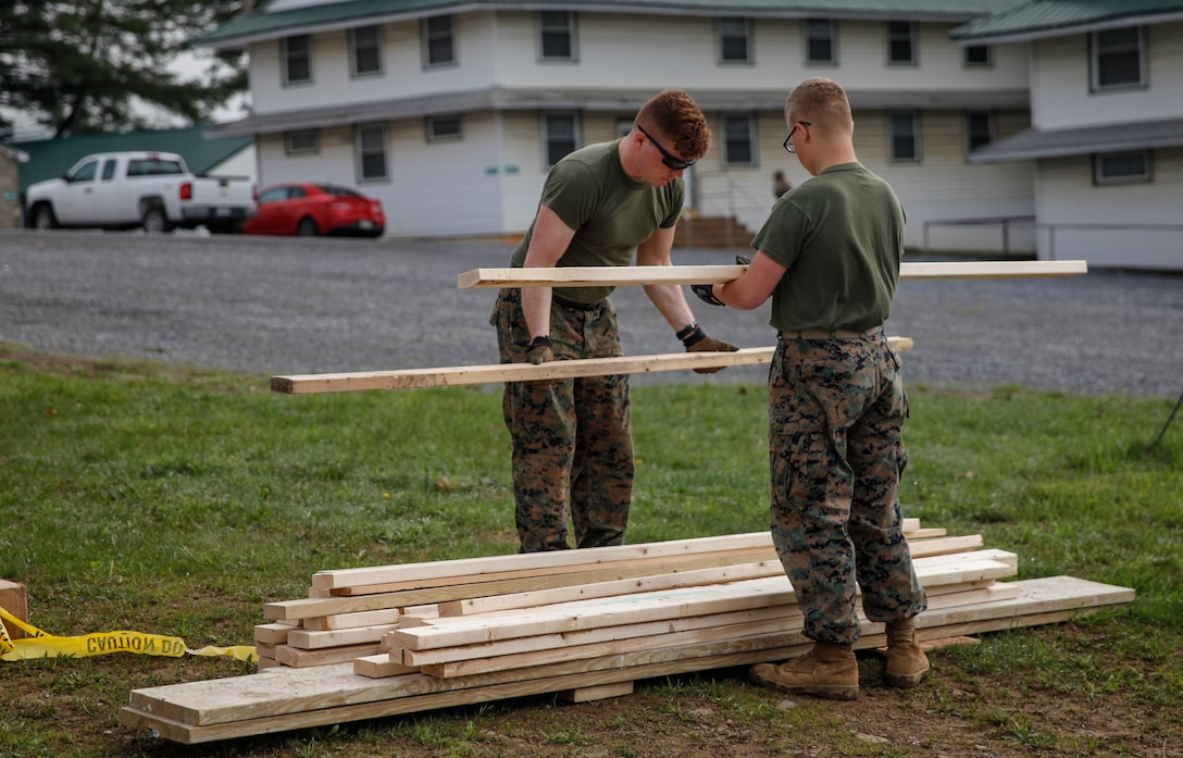 U.S. Marines Lance Cpl. Jason P. McWhinnie (left), field radio operator with Engineer Support Company, 6th Engineer Support Battalion, 4th Marine Logistics Group, and Private First Class Austin T. Roberts (right), combat engineer with Bridge Company C, 6th ESB, 4th MLG, stack wooden planks at a construction site during exercise Red Dagger at Fort Indiantown Gap, Pa., May 20, 2018.