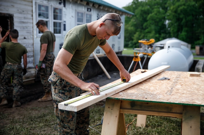 U.S. Marine Private First Class Jeffrey Beasley, combat engineer with Engineer Company C, 6th Engineer Support Battalion, 4th Marine Logistics Group, measures and marks a cut line on a plank at a construction site during exercise Red Dagger at Fort Indiantown Gap, Pa., May 20, 2018.