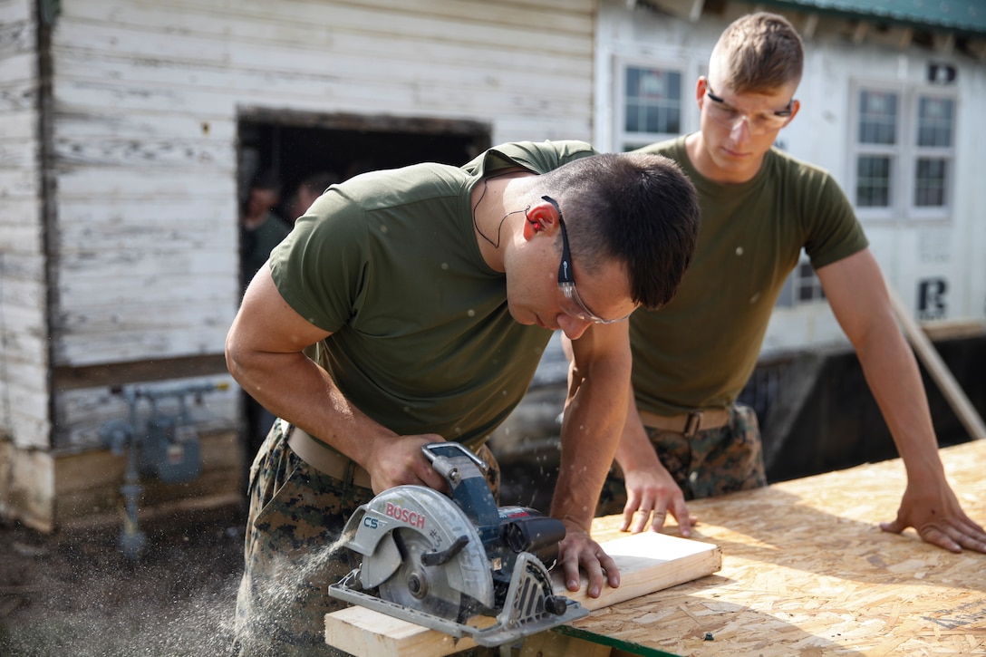 U.S. Marine Lance Cpl. Dylan A. Hudson (left), combat engineer with Engineer Company C, 6th Engineer Support Battalion, 4th Marine Logistics Group, cuts a wooden plank with a circular saw while U.S. Marine Private First Class Jeffrey Beasley (right), combat engineer with ECC, 6th ESB, 4th MLG, holds the table for stability at a construction site during exercise Red Dagger at Fort Indiantown Gap, Pa., May 20, 2018.