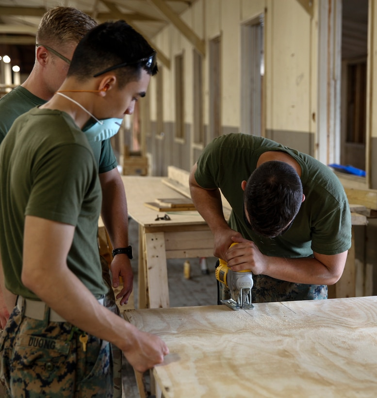 U.S. Marine Lance Cpl. Jacob N. Wooldridge, combat engineer with Bridge Company C, 6th Engineer Support Battalion, 4th Marine Logistics Group, uses a jig saw to cut a piece of plywood at a construction site during exercise Red Dagger at Fort Indiantown Gap, Pa., May 20, 2018.