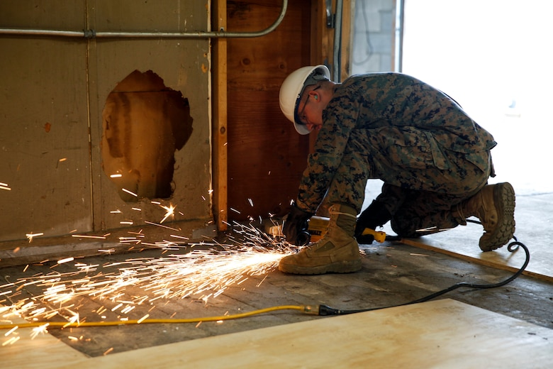 U.S. Marine Lance Cpl. Casey W. Holle, combat engineer with Engineer Company C, 6th Engineer Support Battalion, 4th Marine Logistics Group, uses a grinder to level the ground at a construction site during exercise Red Dagger at Fort Indiantown Gap, Pa., May 20, 2018.