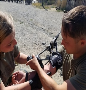 Lance Corporal Shivers of Alpha Company applies an IV on HM3 Ford in a Combat Lifesaving Class.