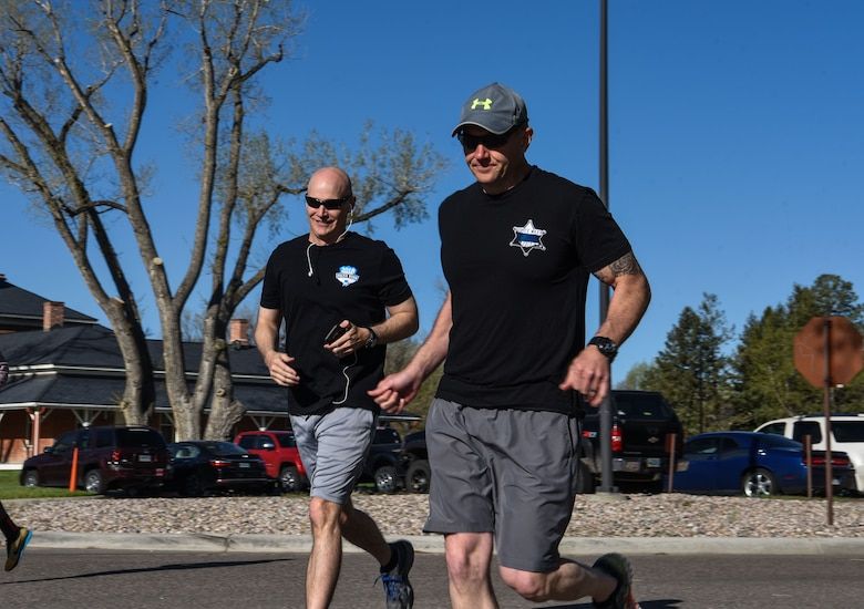 Col. John Grimm, 90th Security Forces Group commander, and Chief Master Sgt. Brian Lewis, 90th SFG chief enlisted manager, run during the Police Week 5k, May 14, 2018, on F.E. Warren Air Force Base, Wyo. More than thirty Airmen came out to support Police Week by participating in the run. In 1962, President John F. Kennedy signed a proclamation which designated May 15 as Peace Officers Memorial Day and the week in which that date falls as Police Week. People all across the United States participate in various events which honor those who have paid the ultimate sacrifice. (U.S. Air Force photo by Airman 1st Class Braydon Williams)