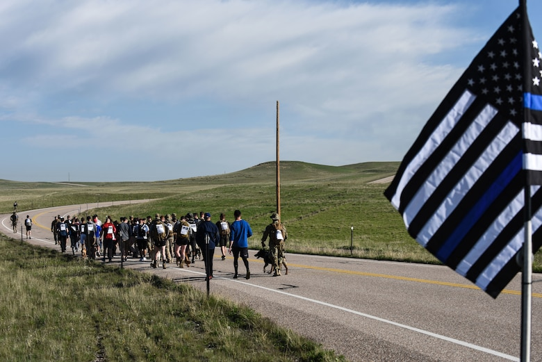 Airmen from the 90th Missile Wing begin the run, walk or ruck for Police Week, May 17, 2018, on F.E. Warren Air Force Base, Wyo. The Police Week run, walk or ruck was a six-mile course around the northern perimeter of the base. To place in the competition each Airmen's ruck had to weigh 35 pounds. In 1962, President John F. Kennedy signed a proclamation which designated May 15 as Peace Officers Memorial Day and the week in which that date falls as Police Week. People all across the United States participate in various events which honor those who have paid the ultimate sacrifice. (U.S. Air Force photo by Airman 1st Class Braydon Williams)