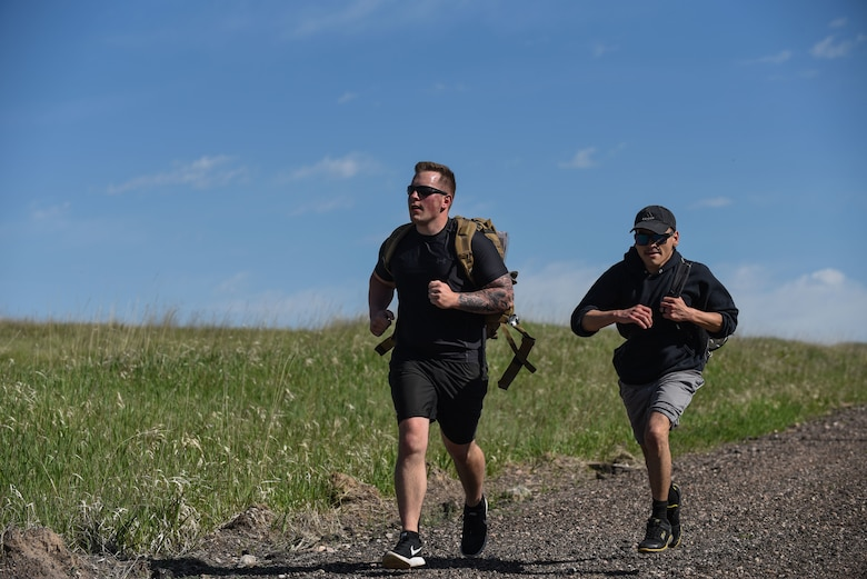 Senior Airman Tyler Hiltner, 90th Security Forces Group defender, and Senior Airman Francisco Chavez, 90th SFG defender, race to the finish line of the six-mile run, walk or ruck for police week, May 17, 2018, on F.E. Warren Air Force Base, Wyo. The Police Week run, walk or ruck was a six-mile course around the northern perimeter of the base. To place first, second or third in the competition, each Airmen's ruck had to weigh 35 pounds. In 1962, President John F. Kennedy signed a proclamation which designated May 15 as Peace Officers Memorial Day and the week in which that date falls as Police Week. People all across the United States participate in various events which honor those who have paid the ultimate sacrifice. (U.S. Air Force photo by Airman 1st Class Braydon Williams)