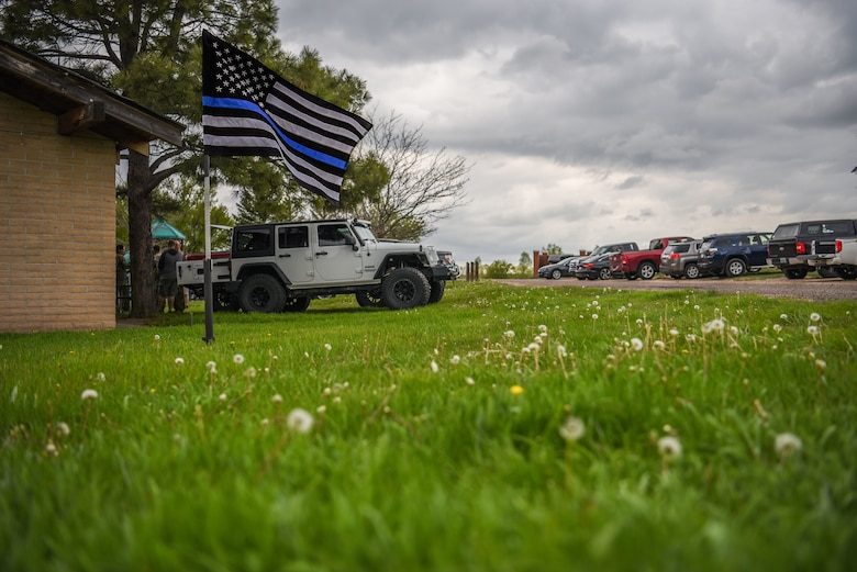 The Thin Blue Line Flag waves in the wind during a barbecue for the closing of Police Week, May 18, 2018, on F.E. Warren Air Force Base, Wyo. Police Week concluded with festivities for Airmen and families to unwind after a week of events and work. In 1962, President John F. Kennedy signed a proclamation which designated May 15 as Peace Officers Memorial Day and the week in which that date falls as Police Week. People all across the United States participate in various events which honor those have paid the ultimate sacrifice. (U.S. Air Force photo by Airman 1st Class Braydon Williams)