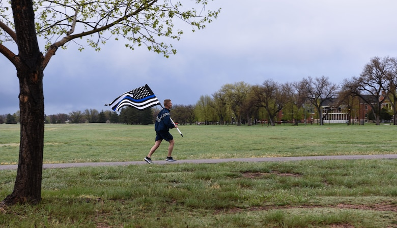1st Lt. Justin Fitzwater, 90th Security Support Squadron defender, runs with the thin blue line flag during a twenty-four-hour remembrance run for Police Week May 13, 2018, on F.E. Warren Air Force Base, Wyo. The run was held to honor Defenders and civilian police alike who have paid the ultimate sacrifice. Various people from around base came to support the run and keep it going for the full 24 hours. In 1962, President John F. Kennedy signed a proclamation which designated May 15 as Peace Officers Memorial Day and the week in which that date falls as Police Week. People all across the United States participate in various events which honor those who have paid the ultimate sacrifice. (U.S. Air Force photo by Airman 1st Class Braydon Williams)